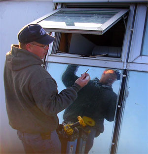 Workman repairs gasketing and hardware on window.