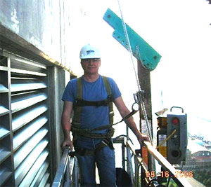 Mark Meshulam, Chicago Window Expert inspects building from scaffold on highrise building
