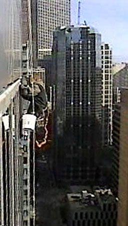 Workman looking for window leak in tall building from bosun's chair