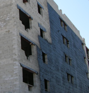Bituminous waterproofing is sprayed on the face of the block backup wall prior to installation of the face brick. Yes!
