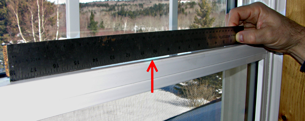 The meeting rail of a vinyl double hung window bows in excess of 1/16