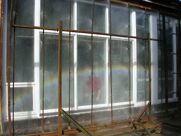 A spray rack is used to apply hurricane-volumes of water to the test specimen while blowers are used to create a negative pressure on the inside. If the specimen sucks in uncontrolled water, the test is a fail, and that sucks because the testing cannot proceed until the leak is diagnosed and fixed.