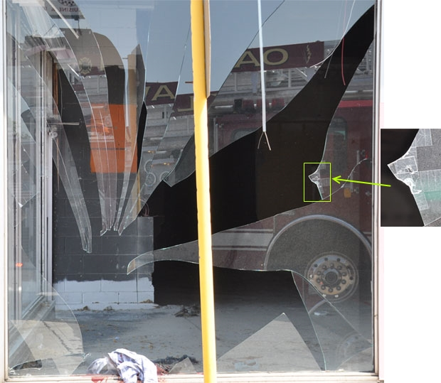 Broken storefront glass with large fragments and inset with tape on prior damage
