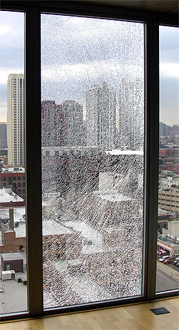 Broken glass in condominium window goes from floor to ceiling