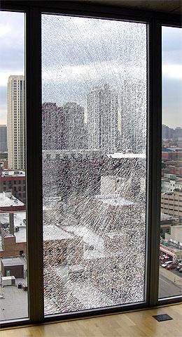 Broken glass in condominium window goes from floor to ceiling