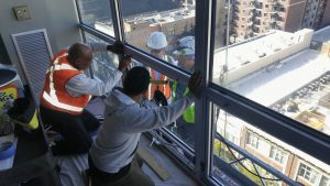 Workmen perform construction forensic investigation of window in high rise building